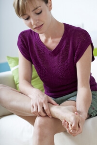 young woman sitting on couch with one leg crossed rubbing her foot