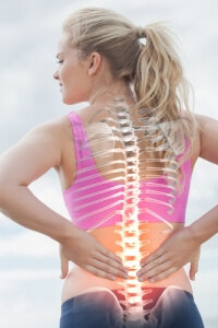 woman holding her lower back, her body is transparent revealing her skeletal spine